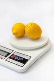 Two yellow lemons on white kitchen digital scale Royalty Free Stock Photo