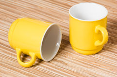 Two yellow mugs on a table Stock Images