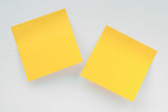 Two yellow notepaper pieces on white canvas Stock Image