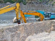 Two yellow and one blue excavators in the ditch at the site of the road construction works. Side view, summer day royalty free stock photography