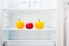 Two yellow and one red peppers on shelf of open empty refrigerator Royalty Free Stock Photo