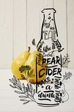 two yellow organic pears on wooden background with illustration of cider bottle and flowers royalty free stock photography