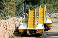Two yellow paddle boats with plastic steps and slides in middle taken out of water for cleaning left in a row next to traditional. Stone wall and dense garden stock photo