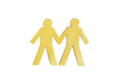 Two yellow paper cut out figures holding hands over white background Royalty Free Stock Image