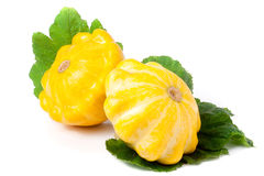 Two yellow pattypan squash with leaf  on white background Royalty Free Stock Images
