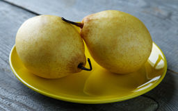 Two yellow pears on the plate on a  table Royalty Free Stock Photo