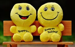 Two Yellow Plushtoy on Brown Bench Royalty Free Stock Photography