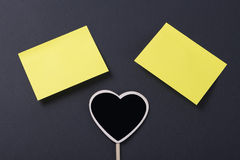 Two yellow post-it jutno to a blackboard with heart shape on black background Stock Photography