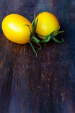 Two yellow ripe tomatoes on wooden table Stock Photos