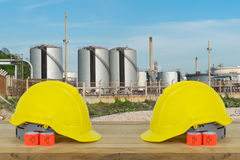 Two Yellow Safety Helmet on wood with oil refinery industry with Royalty Free Stock Image