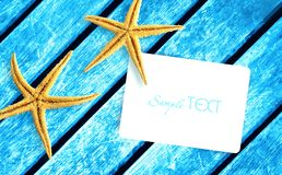 Two yellow sea stars and white paper card on a bright blue wooden rustic background. Royalty Free Stock Image