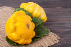 Two yellow squash on a wooden background with napkin of burlap Royalty Free Stock Image