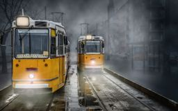 Two yellow streetcars trams at the terminus. On a damp foggy day in Budapest Royalty Free Stock Image