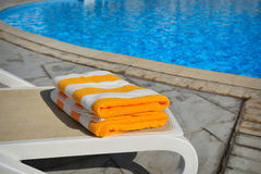 Two yellow striped towels lie on a sun-bed near a swimming pool Royalty Free Stock Image