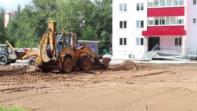 Two yellow tractors work on construction site stock footage