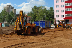 Two yellow tractors work on construction site at summer sunny da Royalty Free Stock Photography