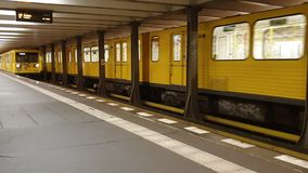 Two yellow trains in Berlin subway, arriving and leaving platform simultaneously