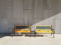 Two yellow vintage benches designed with morning light from the side in the early morning on textured concrete wall background. And floor in with copy space royalty free stock images