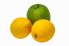 Two yellow wet lemons and one green apple isolated Royalty Free Stock Photo