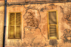Two yellow windows in an old wall in hdr Stock Images