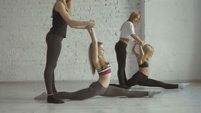 Two Yoga Fitness Girls Help Their Partners To Stretch Legs And Do The Splits. Sport Practice With Partner, White Brick Wall Background, Healthy Lifestyle, 4K stock footage