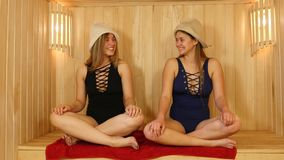 Two Yoga Girls Smiling. Sauna spa therapy beautiful young girls in warm wood room stock video footage