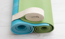 Two yoga mats and belt. Two yoga iyengar mats green and blue colors and white belt Stock Photos