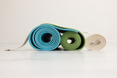 Two yoga mats and  belt. Two yoga iyengar mats green and blue colors and white belt Stock Photo