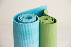 Two yoga mats stacked in the shape of heart. Green and blue colors Royalty Free Stock Images