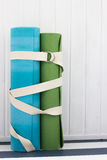Two yoga mats  white belt. Two yoga mats green and blue colors and white belt Stock Photo