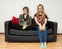 Two yong women are sitting on the sofa Stock Photos