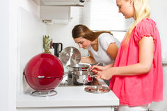 Two youn women in the kitchen. Two girlfriends cooking at home Royalty Free Stock Photography