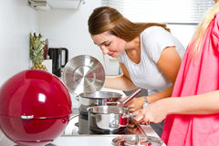 Two youn women in the kitchen Stock Photography