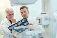 Two yound doctors examining x-ray film at diaphanoscope Stock Image