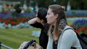 Two younf women relax in a park. Travel photography stock footage