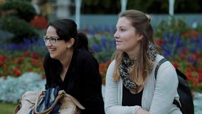 Two younf women relax in a park. Travel photography stock video footage