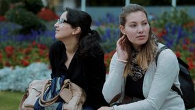 Two younf women relax in a park. Travel photography stock video