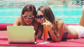 Two young adult women working on laptop together. Two young freelancer women with cocktail working on laptop together in resort on swimming pool background stock video