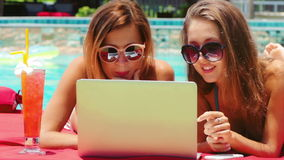 Two young adult women working on laptop together. Two young freelancer women with cocktail working on laptop together in resort on swimming pool background stock footage