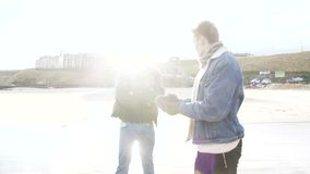 Friends stand and talk on a winter beach. Two young adults stand and talk on a winter beach in Tynemouth stock video footage
