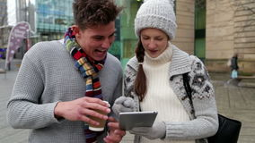 Two young adults using a tablet outdoors. Young man and woman standing in the city using a digital tablet together stock video footage