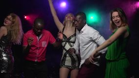 Two young African American men dance with girls. Slow motion. Two young African American men dance with girls in short dresses at the party. In the background stock video footage