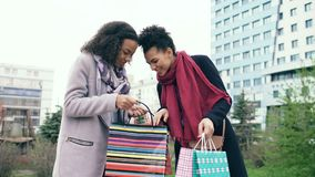 Two young african american women sharing their new purchases in shoppping bags with each other. Attractive girls talking stock image
