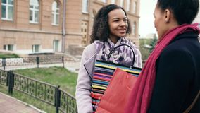Two young african american women sharing their new purchases in shoppping bags with each other. Attractive girls talking. And smiling after visiting mall sale Royalty Free Stock Photography