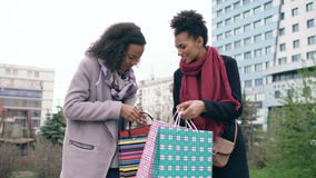 Two young african american women sharing their new purchases in shoppping bags with each other. Attractive girls talking stock video footage
