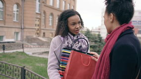 Two young african american women sharing their new purchases in shoppping bags with each other. Attractive girls talking stock footage