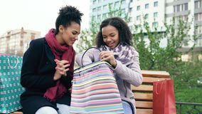 Two young african american women sharing their new purchases in shoppping bags with each other. Attractive girls talking. While sit on steet bench Royalty Free Stock Photos