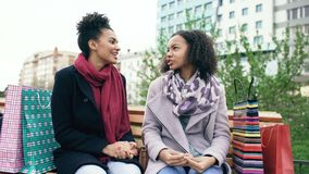 Two young african american women sharing their new purchases in shoppping bags with each other. Attractive girls talking royalty free stock photography