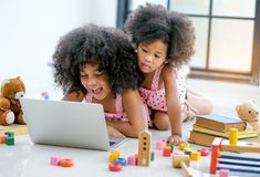 Free Two Young African Girls Play With Notebook Computer Among Toys, Doll And Book In Front Of Glass Window Stock Image - 154226261