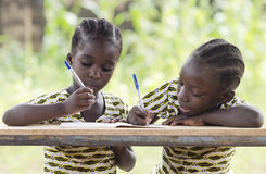 Two young African girls writing outdoors. Young girls sitting at table and writing on paper with color pen Stock Images